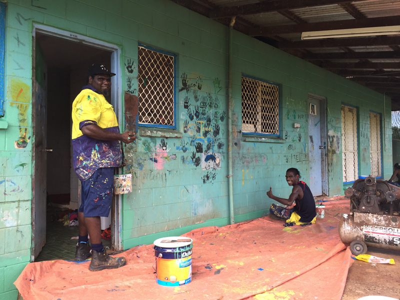 Wadeye community members prepping an area of a house ready to paint