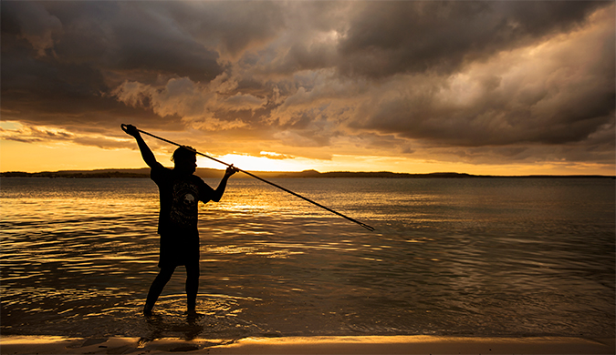 An Aboriginal man spearfishing at a beach.
